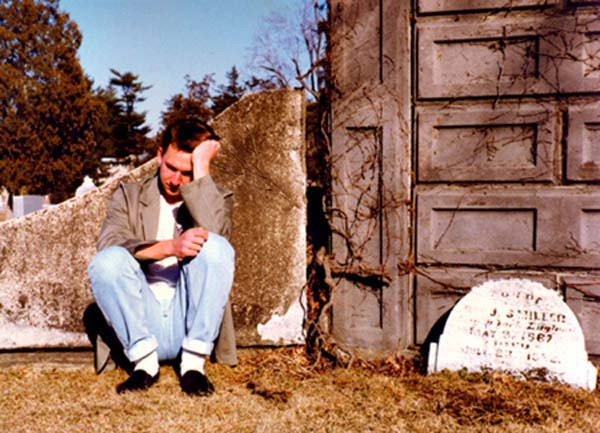 Andy, sitting by a tombstone, photograph copyright © 1988 - 2012 Janet Kuypers