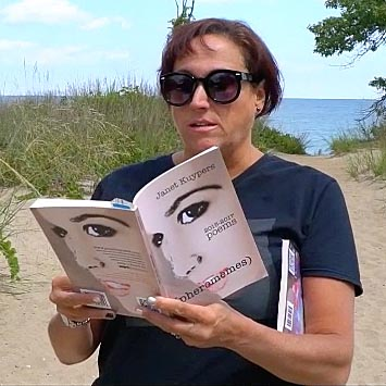 "video still of Janet Kuypers reading from her book ""(pheromemes) 2015-2017 poems"" live"