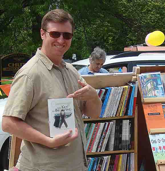 John holding a copy of The Key to Believing at an outdoor art gallery